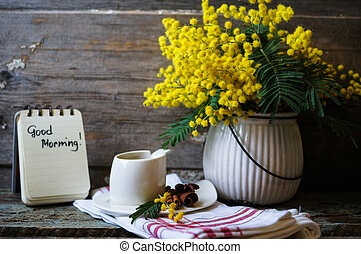 spring time - Glass cup with tea and blooming yellow mimosa...