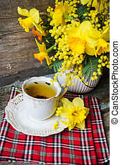 Easter time, spring flowers and cup of tea on the old wooden...