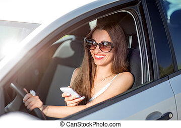 Young smiling woman using phone while driving her car