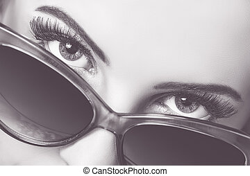 Seductive look over sunglasses - Closeup portrait of a...
