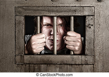 CP of a man behind bars - A CP of a man in prison holding...