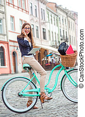 Businesswoman going to work by bicycle speaking phone in old city center background