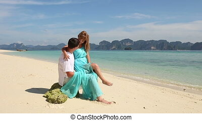 strong guy sits on stone with blonde asian girl
