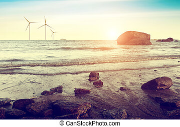 white wind turbine generating electricity on sea - Dusk sea,...