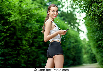 Running woman Female runner relaxing after jogging outdoor...
