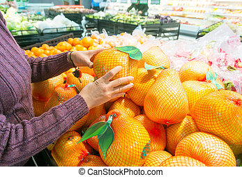Supermarkets - Woman buying fresh fruit at the supermarket