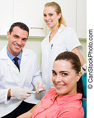 dental care - a smiling patient in a dentist chair with a...