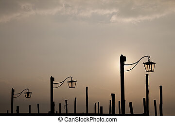 Lampposts silhouette. - Silhouette of three lampposts at...