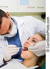 dental surgery - a dentist performing dental surgery on a...