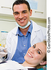 dentist - a male dentist checking his female patient
