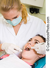 female dentist - a female dentist giving her patient a...