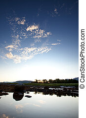 Sky Reflection - A calm pool of water reflection the...