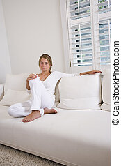 Teenage girl at home relaxing in white room