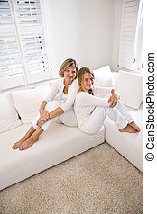 Mother and teenage daughter relaxing at home in white living...