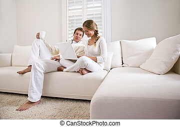 Father and teenage daughter on white living room sofa using...