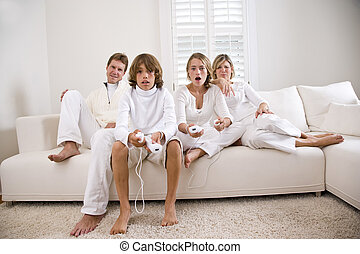 Children playing video game on white sofa with parents...