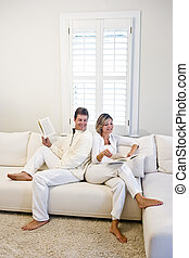 Mature couple relaxing and reading together on white living room sofa