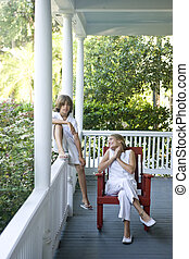 Brother and sister relaxing on porch