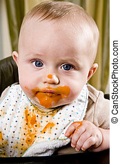 Messy baby wearing bib after eating solid food - Messy six...