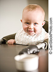 Baby in high chair ready to eat - Six month old baby in high...