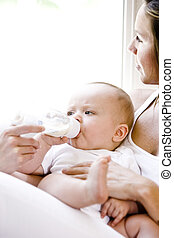 Close up of mother feeding bottle to baby