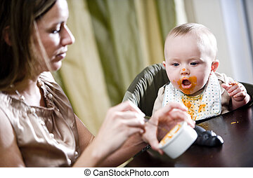 Mother feeding hungry baby solid food