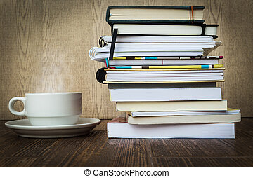 Books stacked and coffee with steam on a wooden table