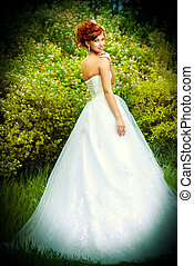 wedding - Lovely elegant red-haired bride stands on the lawn...