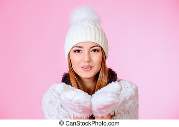 mitten - Cute joyful girl in warm knitted clothing blowing...