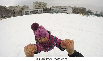 Happy Child Rotates and Fall on the Snow
