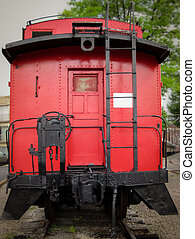 Red Caboose - Bright red caboose at the rear of a train on...