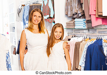 Cute girl with her mother in white outfit at shop