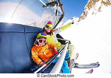 Mom with boy on ski lift ropeway chair - little happy boy...