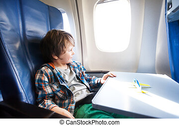 Happy boy sit in plane with toy model on table - Little boy...