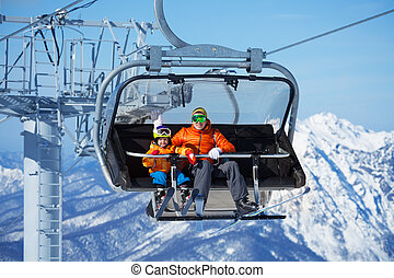 Father and boy sit in ski lift over mountains - Father and...