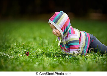 Toddler and butterfly - Curious baby in striped dress...