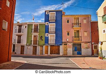 Mediterranean village street with colorful facades under...