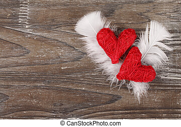 Two red hearts with feathers