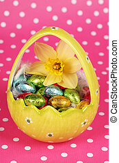 Yellow big easteregg with small colourful chocolate eggs