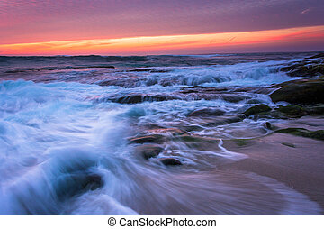 Waves and rocks in the Pacific Ocean at sunset, in La Jolla, Cal
