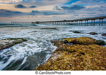 Waves crashing on rocks and the fishing pier in Ocean Beach,...