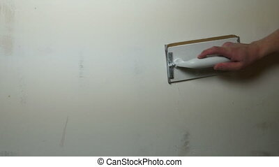 Man Hand Sanding Plaster Wall, close up