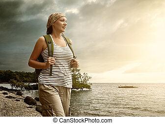 Tourist girl enjoying view of beautiful sunset and sea. -...