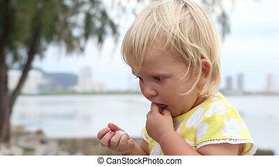 little blonde child eats closeup - closeup little blonde...