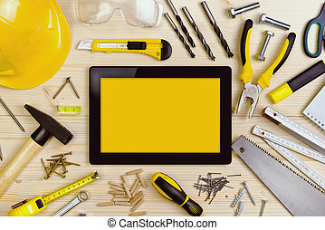 Digital Tablet and Assorted Carpentry Tools on Workshop...