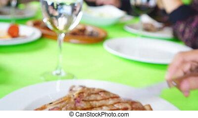 Sliding camera to t-bone steak plate in restaurant - Closeup...