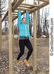 Pretty girl training on monkey bars - Pretty smiling girl...