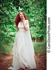 Beautiful redhead woman wearing white dress, in a forest -...