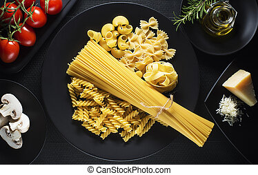 Pasta - Raw mixed pasta on black background overhead shoot