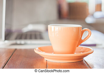 Orange coffee cup on work station, stock photo